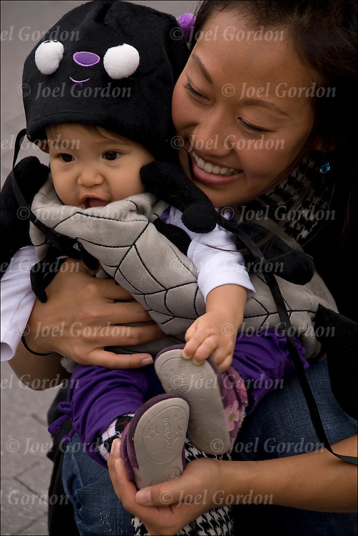 Mother holding,  smiling, affectionately at her toddler in the Washington Square Park