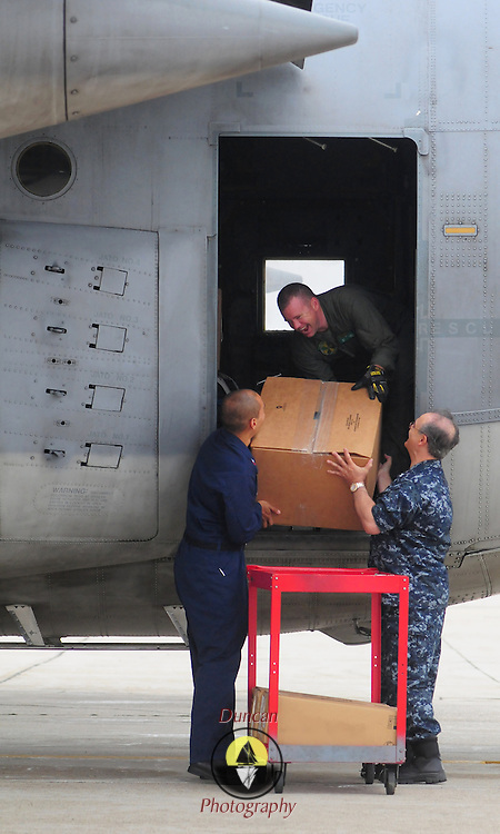 7/25/09 -- BRUNSWICK, Maine. U.S. Navy Reserve Petty Officers Leo Villani, right, and James Rincon pass aboard the last cases of gear to Chief Eric Lowrie. VR-62's last C-130 Hercules headed to Jacksonville, Fla. today as part of the BRAC realignment. The squadron has a few members on duty through August at Brunswick, but has finished their mission here. Photo by Roger S. Duncan.