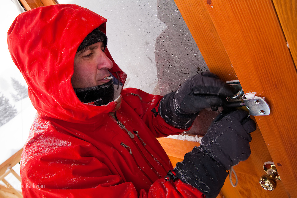 Benet Sommers uses a screwdriver to get the latch off a frozen lock at the Fowler-Hillard yurt in Colorado.  Luckily the latch had the screws facing out so it was easy to take them out.