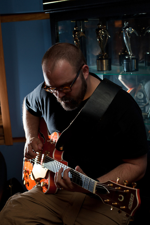 A man (B Pelon) plays an electric guitar in a recording studio.