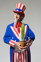 "Uncle Sam holding a small green plant in a pot.  Uncle Sam going ""Green""...Model Release: 20080626_MR_A"