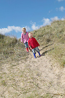 Brother and sister (4-6) standing on sand dunes