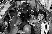 Three teenagers working inside a kiosk at the IDP Charahi Qambar refugee camp.