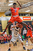 Danbury High School's Jordan Alleyne leaps over Trumbull High School's Joseph Nemchek to try and avoid fouling him during a boys basketball game played at Trumbull High School, Trumbull, CT on Friday, January 22, 2016.