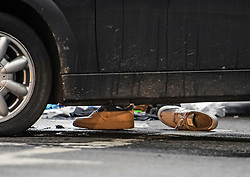 © Licensed to London News Pictures. 24/11/2019. London, UK. A pair of shoes lie on the ground next to a car involved in a collision, at the scene where a man has been found stabbed to death outside a west London train station. The attack follows a stabbing in Whitechapel on Saturday, in which another man in his 20s was killed. Photo credit: Ben Cawthra/LNP
