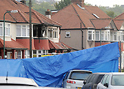 © Licensed to London News Pictures. 23/09/2011. LONDON, UK. A blue plastic tarpaulin is used to shield the scene. Six people, including three children, two teenagers and an adult have died following a house fire in Neasden, North West London today (24 Sept 2011). Emergency services were called tot he blaze in the early hours of the morning. Photo credit:  Stephen Simpson/LNP