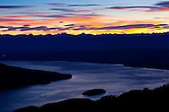 A colorful sunrise emerges above lake TeAnau as seen from the Kepler Trak in Fiordland National Park in New Zealand's South Island.