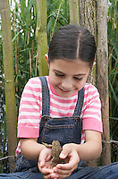 Girl (5-6) holding toad by fence