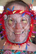 Pat Jolly tries on a Cajun mask at Jazz Fest; 2010 New Orleans Jazz & Heritage Festival