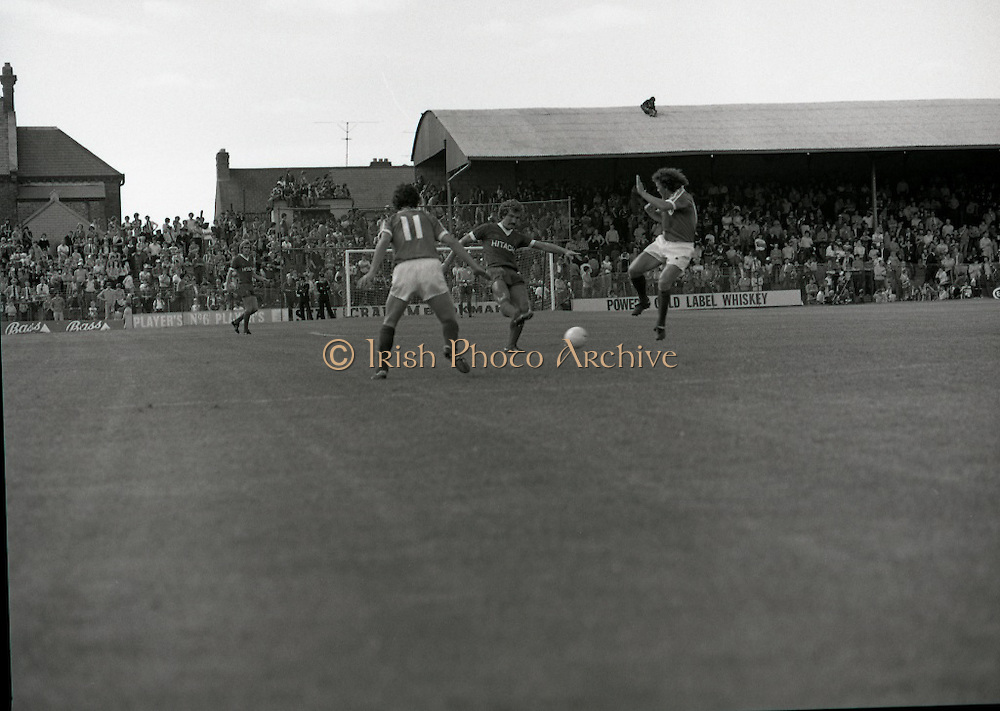 League of Ireland vs Liverpool FC.    (M87)..1979..18.08.1979..08.18.1979..18th August !979..In a pre season friendly the League of Ireland took on Liverpool FC at Dalymount Park Phibsborough,Dublin. The league team was made up of a selection of players from several League of Ireland clubs and was captained by the legendary John Giles. Liverpool won the game by 2 goals to nil..The scorers were Hansen and McDermott...Graeme Souness is pictured firing in a shot at the Irish goal despite the attempts of the Irish defence.