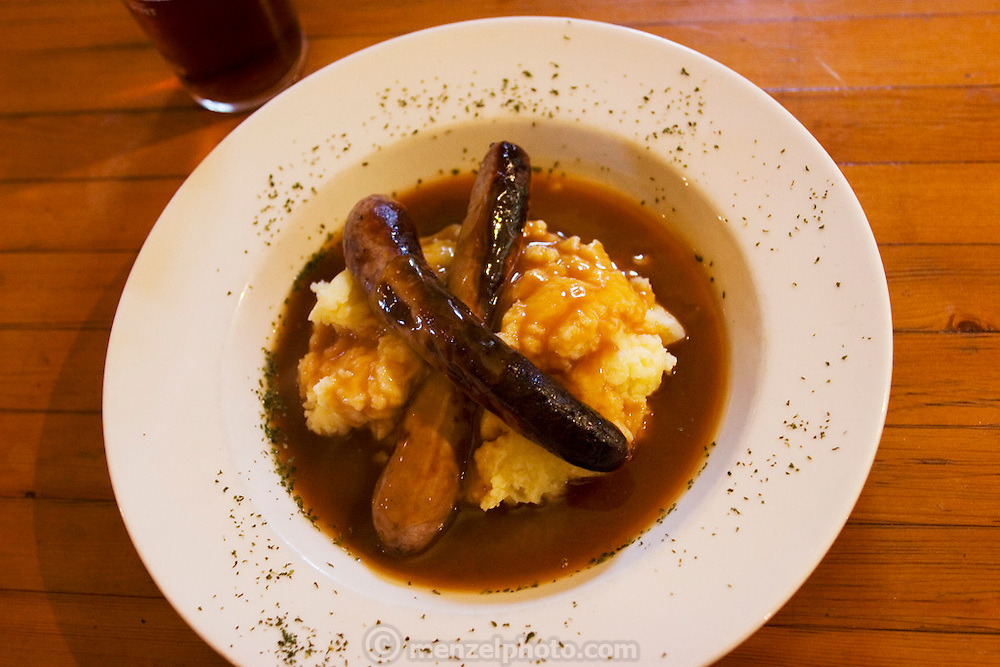 Close up of pub lunch plate of bangers and mash.  White Horse Inn at Hascomb, UK. Lunch with Richard and Fenella Hodson, Godalming, UK. (Material World Family from Great Britain UK) and photographer David Reed.