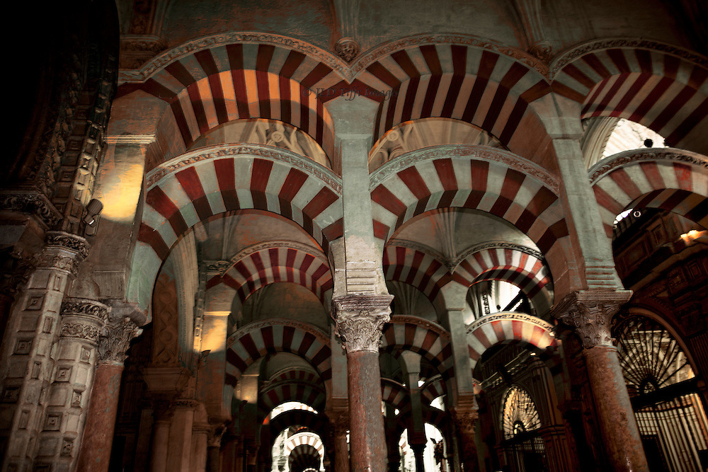 Interior of the Mezquita, or Grand Mosque of Cordoba, showing its forest of columns and overlapping banded arches.  Shadowed, mysterious, and dignified.