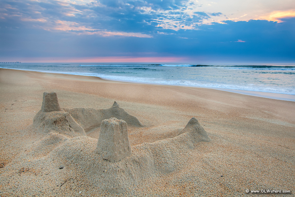 The sun rising behind a sandcastle on the beach at Kill Devil Hills on the Outer Banks of North Carolina.