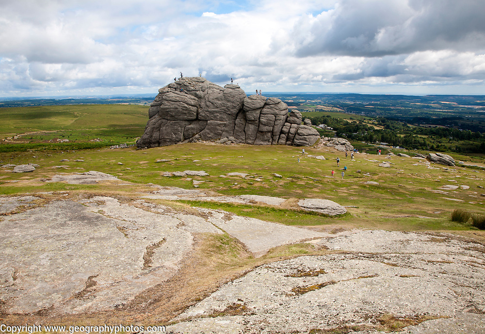 People scrambling on the granite tor of Haytor, Dartmoor national park, Devon, England, UK