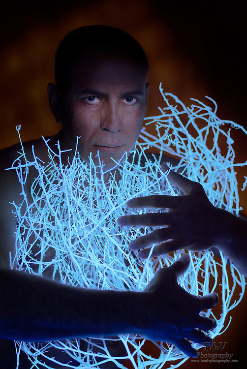 Portrait of a man holding a glowing tumbleweed.Black light