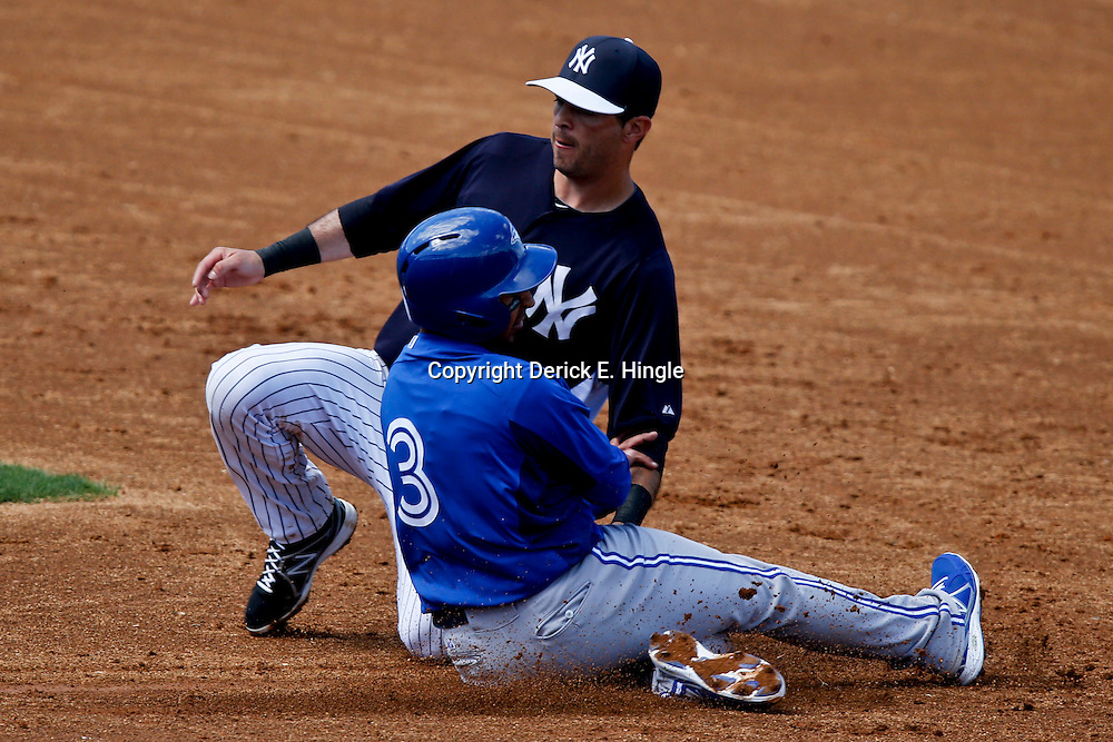 Feb 28, 2013; Tampa, FL, USA; Toronto Blue Jays shortstop Maicer Izturis (3) is tagged out while attempting to steal second base by New York Yankees shortstop Gil Velazquez during the top of the third inning of a spring training game at George Steinbrenner Field. Mandatory Credit: Derick E. Hingle-USA TODAY Sports
