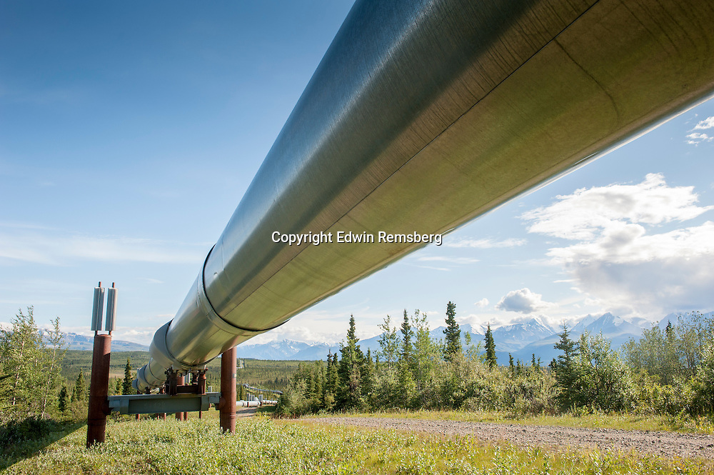 Trans-Alaska Pipeline (Alyeska pipleline) running through landscape with Mountain range in the distance in Alaska.