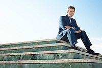 Young man wearing suit sitting on marble staircase outdoors portrait.