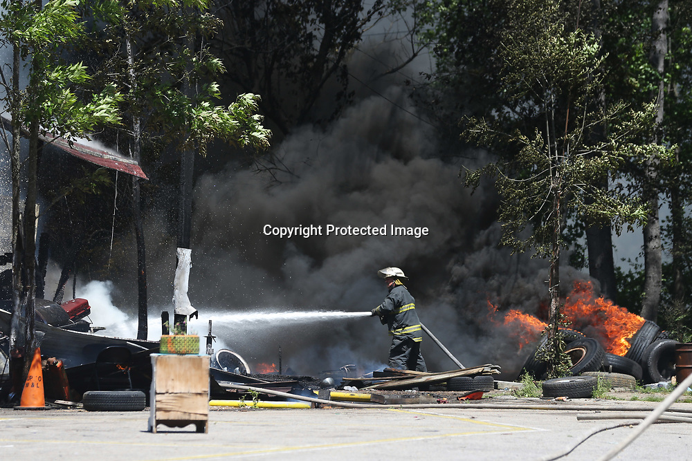 A firefighter with the Mooreville-Eggville Volunteer Fire Department responds to a fire at General Lee Tire on MS-178 in Mooreville Monday afternoon.
