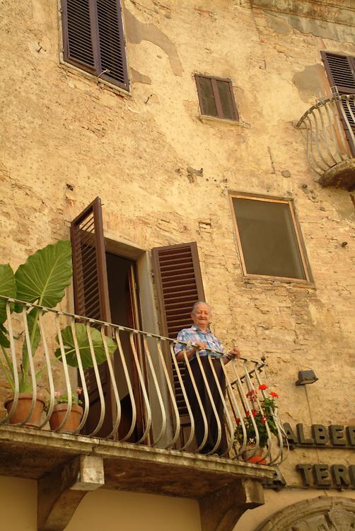 Man on balcony in Cortona, Italy
