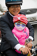 A motorcyclist carries a child in Hanoi, Vietnam.