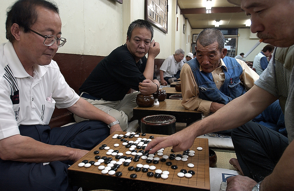GO - Japanese men take time out from World Cup to enjoy a much more traditional scoring game in Kamagasaki District..Osaka Japan 20/06/02..©David Dare Parker/AsiaWorks Photography