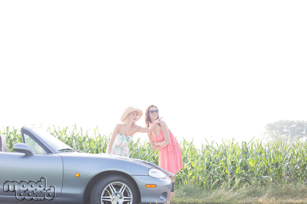 Woman showing something to female friend while reading map on convertible