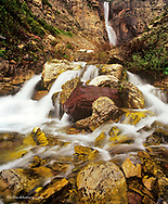 Colorful rocks line Apikuni Falls in Glacier National Park, Montana, USA