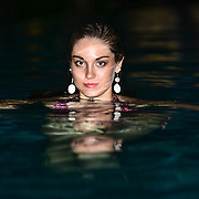 Young woman swimming in the swimming pool at night looking above the water.