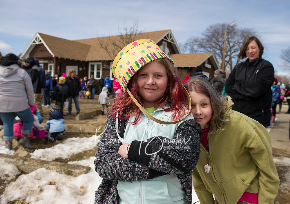 Abby Doten's Easter basket doubles as her Easter bonnet as she waits with her twin sister Ella for Laconia Parks and Recreation egg hunt to begin at Leavitt Park on Sunday afternoon.  (Karen Bobotas/for the Laconia Daily Sun)