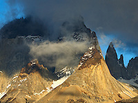 The majestic Cuernos del Paine of Chile's Torres Del Paine National Park, emerge from the clouds and are illuminated in the morning light.