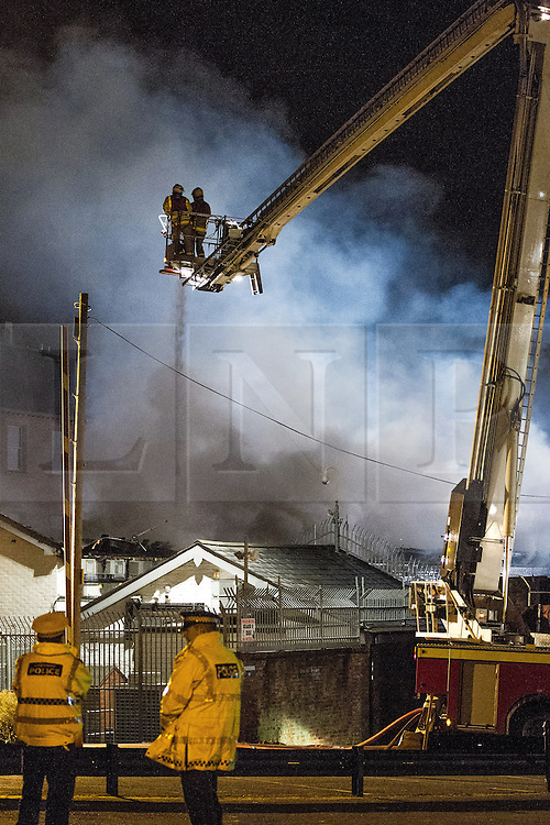 © Licensed to London News Pictures . 13/03/2013 . Alderley Edge , Cheshire , UK . Fire crew on an elevated platform douse flames which have burned out the roof at the rear of the venue . Famous celebrity nightclub , Panacea , in Alderley Edge , is ablaze tonight (12th March) . Fire crews and police were initially called to the venue at 22:30 on Tuesday night (12th March) . Around 50 fire-fighters from Cheshire and Greater Manchester worked to control the fire at the venue , which is adjacent to a petrol station and residential properties in the affluent village of Alderley Edge . This is the second time in five years the venue has been destroyed by fire , previously following a £3.2 million refurbishment in September 2008 . Photo credit : Joel Goodman/LNP