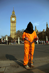 21 April 2011. London, England..A Guantanamo Bay protester stands outside Big Ben and the Houses of Parliament, part of the Royal wedding route the procession will pass en route to Buckingham Palace in the run up to Catherine Middleton's marriage to Prince William. The police have threatened to remove protestors from Parliament Square before the big day..Photo; Charlie Varley.
