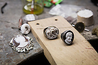 "TORRE DEL GRECO, ITALY - 13 JULY 2016: (L-R) A cameo representing Queen Elizabeth II, a ""See No Evil"" cameo dark ring and a cameo ring representing master-carver and Amedeo Scognamiglia are shown here in the RFMAS workshop, the design studio of Amedeo Scognamiglio and Roberto Faraone Mennella in Torre del Greco, Italy, on July 13th 2016.<br /> <br /> Amedeo Scognamiglio learned the art of carving of cameos at the age of 16 years old in his father's company (M+M Scognamiglio), continuing an artistic manufacturing tradition of a six generations family of coral and cameo manufacturers dating back to the early 1800s in Torre del Greco, a town at the foot of Mount Vesuvius, Italy. Amedeo's design philosophy aims at a contemporary approach to the ancient art of cameo making, through alternative materials, unexpected ideas and smile-triggering designs. In 2001, Amedeo Scognamiglio partnered with his long-time childhood friend Roberto Faraone Mennella to create a fine jewelry line called Faraone Mennella by R.F.M.A.S. Group.The designer duo created a line that brings together the quality and craftsmanship of fine Italian jewelry to the world of fashion accessories. In 2006, the opening of AMEDEO, a Boutique on the chic Upper East Side in NYC, dedicated to the Designer's vision of Cameos, and followed shortly after by another opening in Capri, Italy."