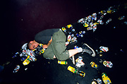 Punk asleep amoungst  litter and beer cans on the floor at a gig. London Astoria 1998