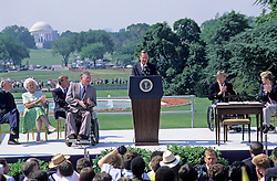United States President George H. W. Bush makes remarks prior to signing the Americans with Disabilities Act of 1990 into law during a ceremony on the South Lawn of the White House in Washington, D.C. on July 26, 1990. Pictured, on stage, (left to right): Reverend Harold Wilke, first lady Barbara Bush, U.S. Vice President Dan Quayle, Evan Kemp, President Bush, Justin Dart, and Sandra Parrino. The act prohibited employer discrimination on the basis of disability. Credit: Ron Sachs / CNP /ABACAPRESS.COM