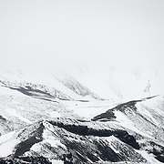 Snow-covered moutnains behind the former whaling station at Whalers Bay on Deception Island. Deception Island, in the South Shetland Islands, is a caldera of a volcano and is comprised of volcanic rock.