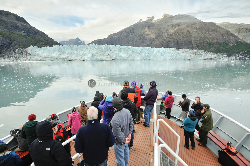 Passengers on the bow of a small cruise ship in front of the Margerie Glacier, Glacier Bay National Park, Alaska.