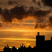 The silhouette of Brussels skyline at sunset against a golden sky with a few clouds.
