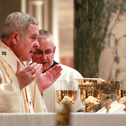 Archbishop Robert J. Carlson prayed the Our Father during the Fortnight for Freedom Mass July 2 at the Cathedral Basilica of St. Louis. Assisting the archbishop was Father Nicholas Smith, who serves as master of ceremonies and director of worship for the archdiocese.