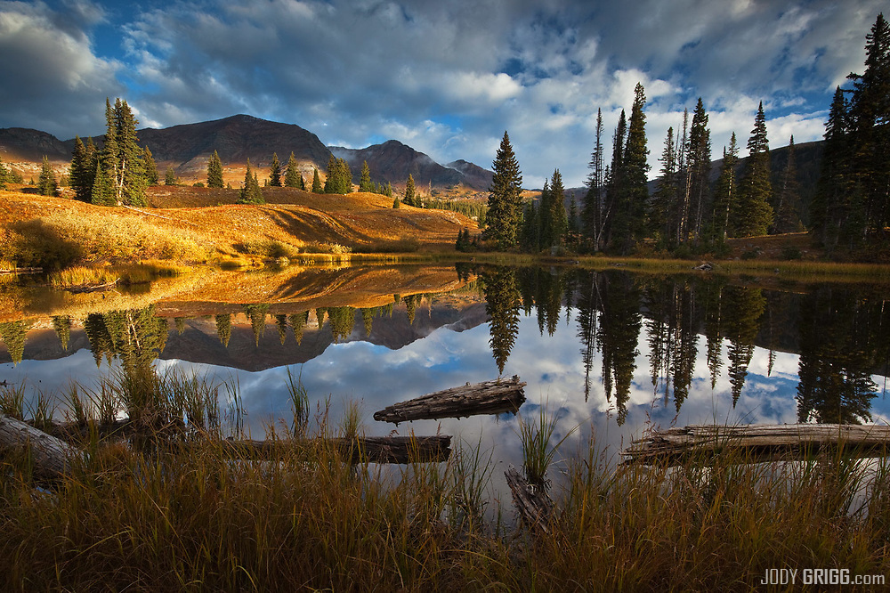 Ruby Peak and Mount Owen reflect in a pond near Lake Irwin outside of Crested Butte in the Elk Mountains