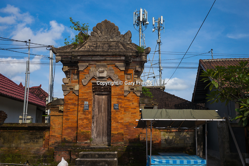 Traditional compound entrance in front of modern communication towers - Bali revisited February 2017