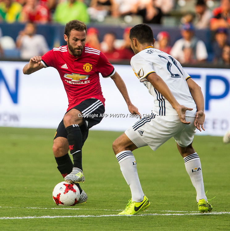 Manchester United Juan Mata, left, moves the ball against Los Angeles Galaxy during the first half of a national friendly soccer game at StubHub Center on July 15, 2017 in Carson, California.   AFP PHOTO / Ringo Chiu