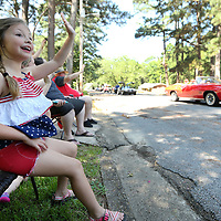 Lennox Coon, 6, of Tupelo, waves to a friend as they pass her home in the Joyner Neighborhood Fourth of July Parade Wednesday morning in Tupelo.