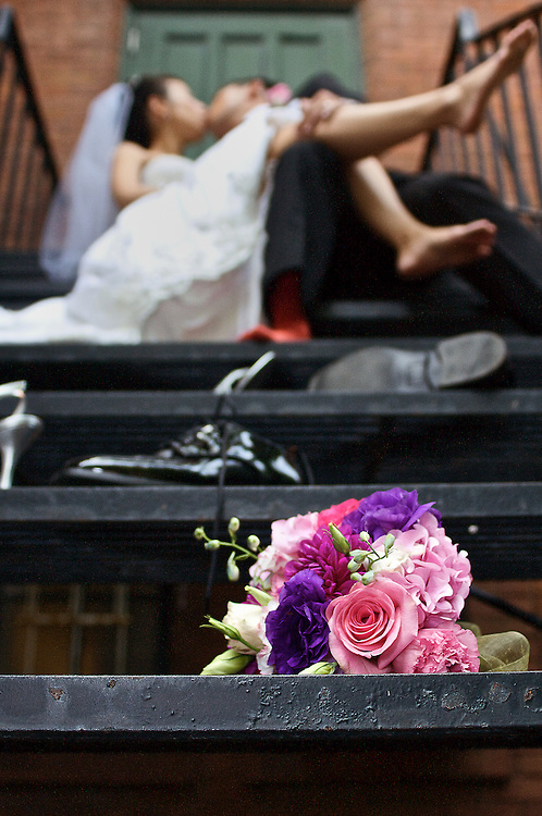 Newlyweds passionately kiss on a fire escape after kicking of their shoes.
