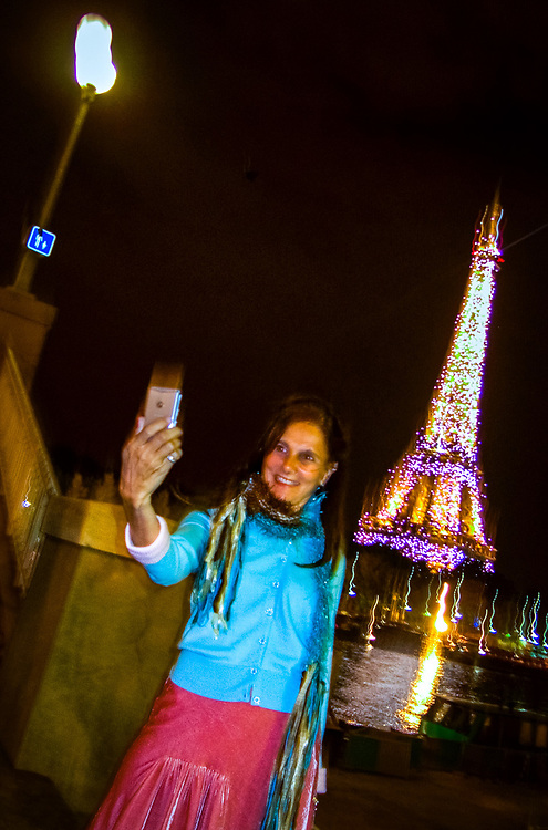 Woman tourist using Cell Phone Camera, self-portrait at night, Eiffel tower in background, Paris