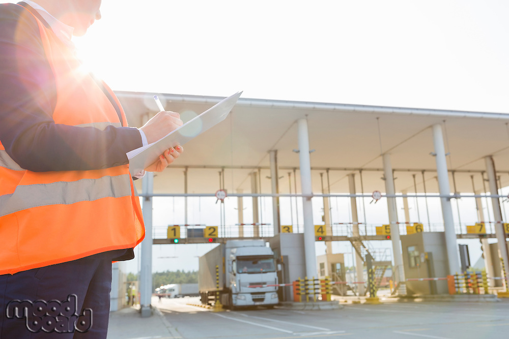 Midsection of female worker writing on clipboard while looking at truck entering in shipping yard