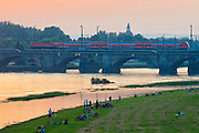 Sonnenuntergang Elbe mit Marienbrücke, Menschen auf Elbwiesen, Dresden, Sachsen, Deutschland.|.sunset on river Elbe, Dresden, Germany
