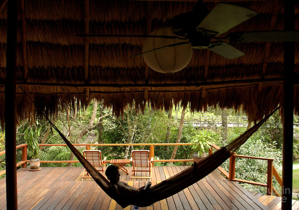 Chris Thompson relaxes in his villa's hammock at the Blancaneaux Lodge, one of Francis Ford Coppola's resorts, in the eastern part of Belize.<br />JUSTIN LANE FOR THE NEW YORK TIMES