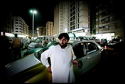 Portraits of Jan Piresa, 42, from Peshawar, A Pakistani a Taxi driver in Abu Dhabi with his taxi in Central  in Abu Dhabi. Photo by Andrew Parsons/i-Images